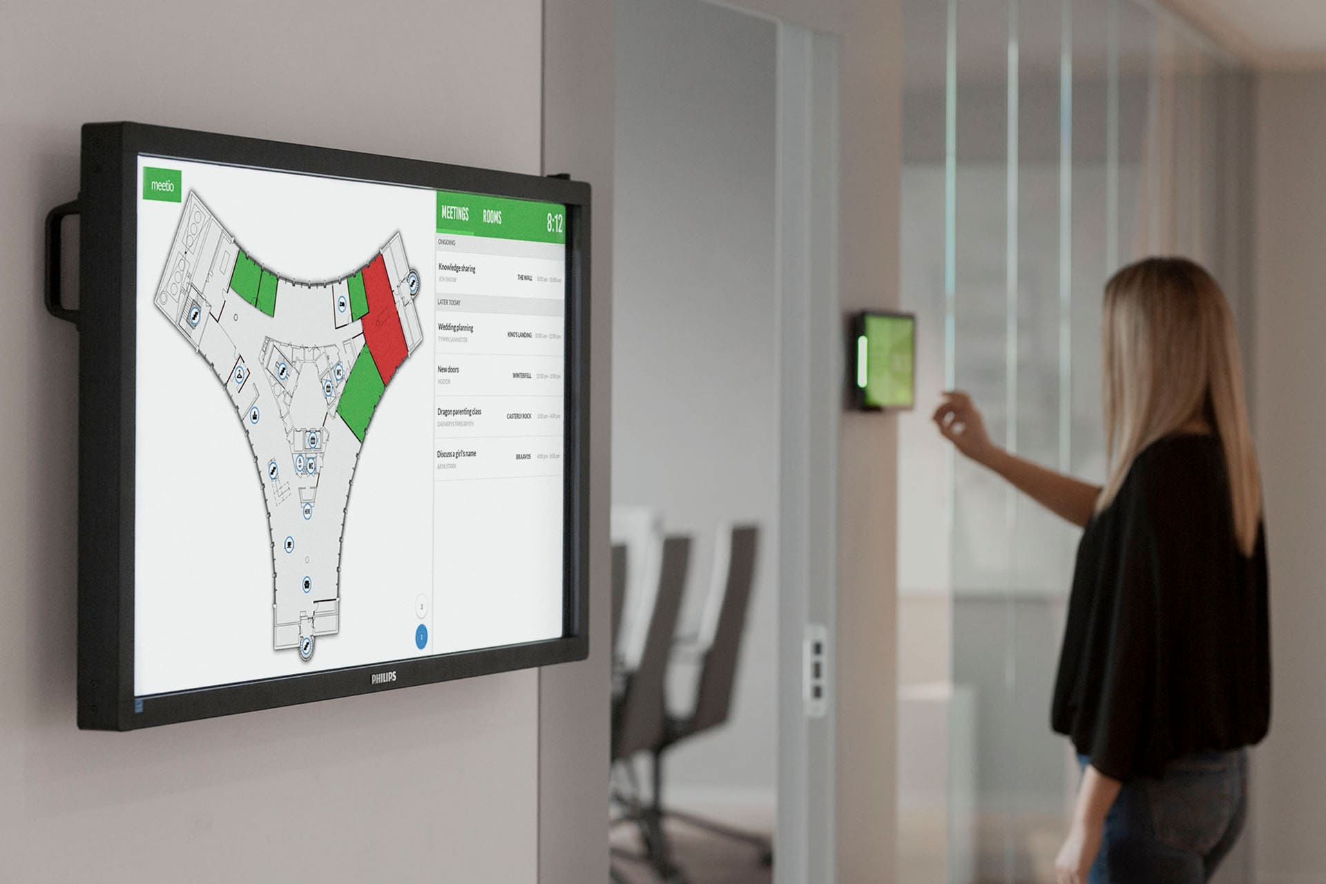 Woman booking a meeting room on a room display