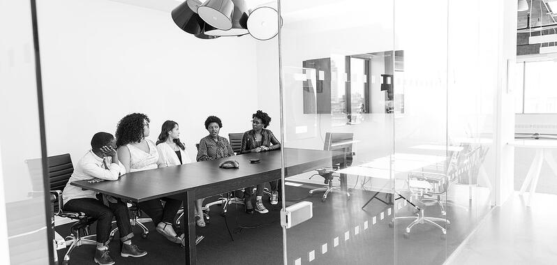 Five women in a meeting room with glass walls