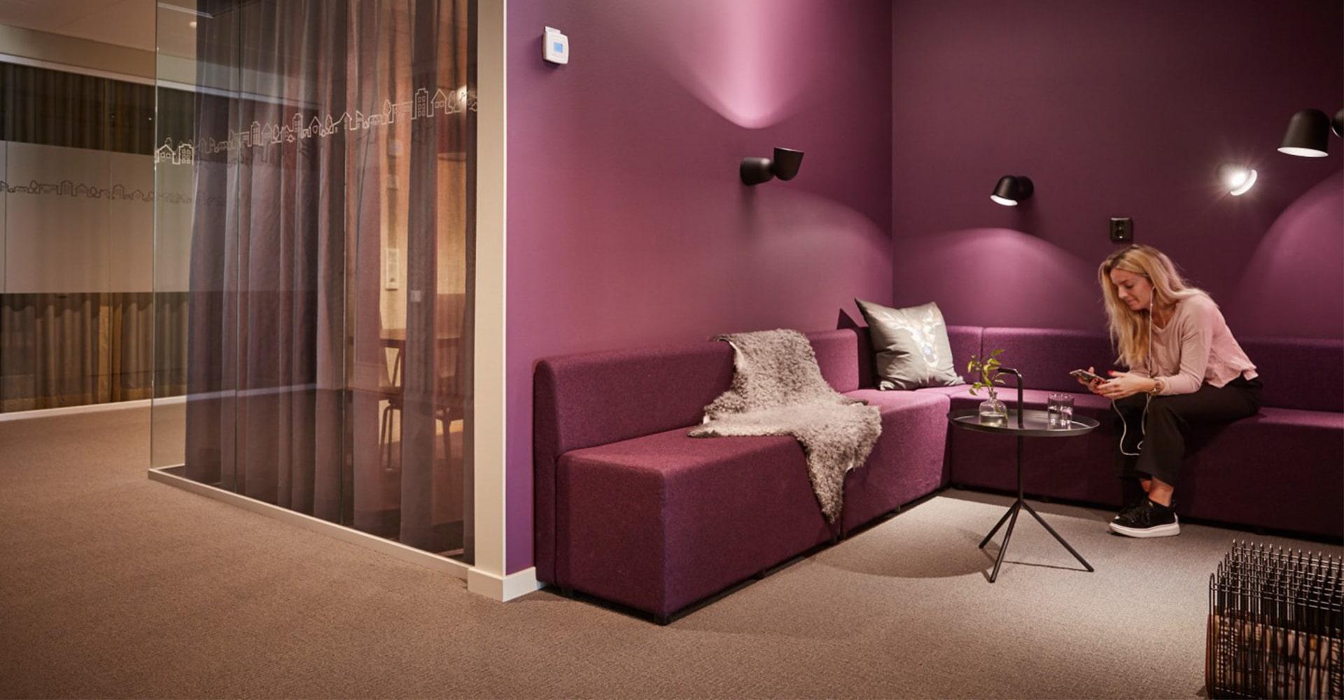 Lila lounge-område på HSB Göta:s kontor
