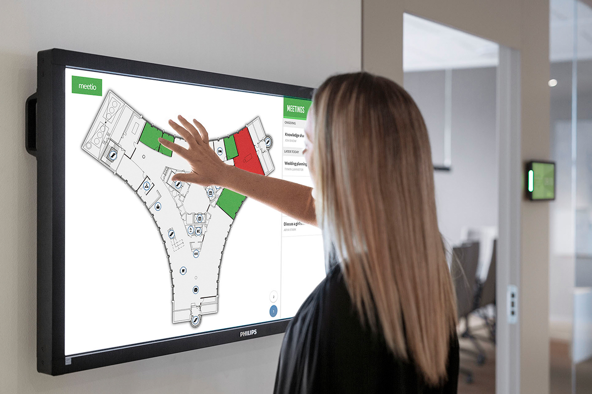 Woman booking a meeting room on a large Philips touch screen
