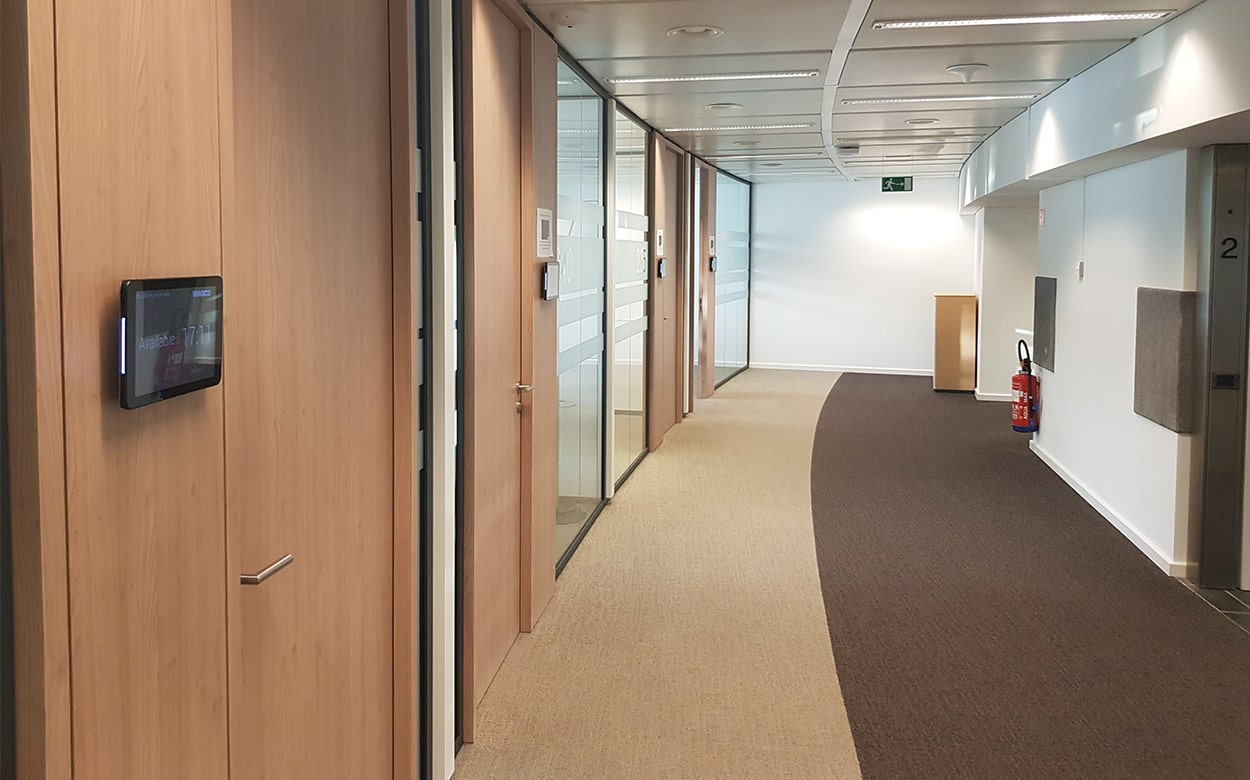Corridor at Wabco with meeting rooms and Meetio Room tablets
